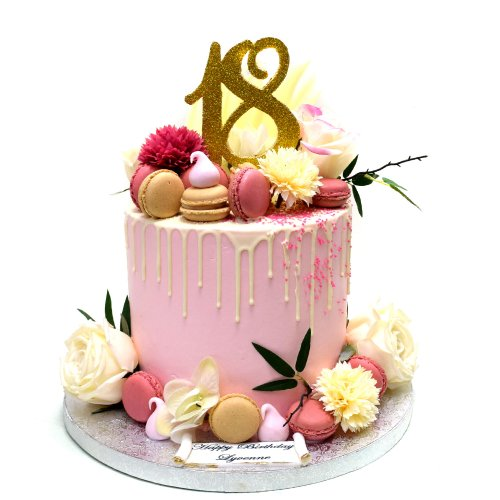 Dripping cake with macarons and flowers