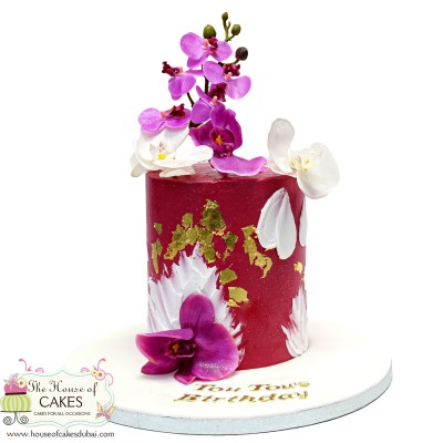 Red and gold buttercream cake with orchids