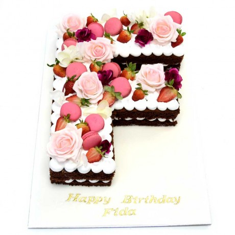 chocolate letter shaped cake with flowers and macarons 8