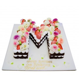 Chocolate letter shaped cake with flowers and macarons