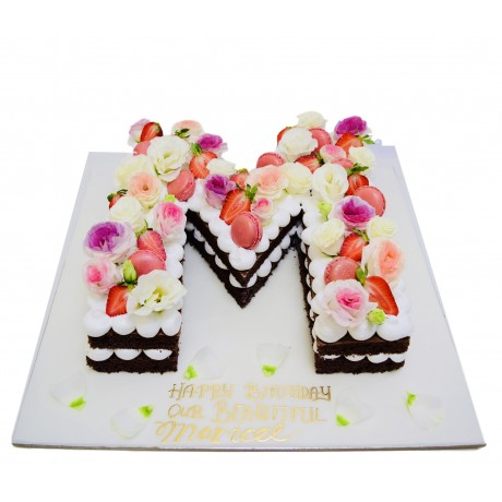 chocolate letter shaped cake with flowers and macarons 6