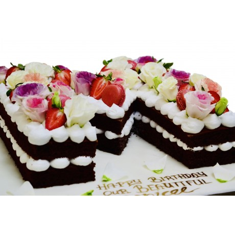 chocolate letter shaped cake with flowers and macarons 7