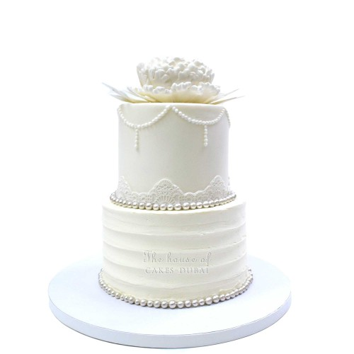 Pretty white cake with lace and flower