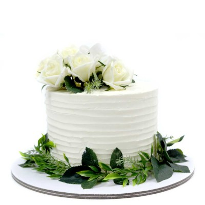 White cream cake with green leaves and white roses