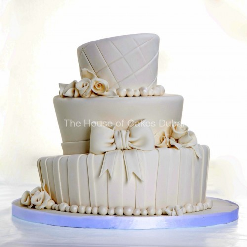 White topsy turvy cake with bow and roses