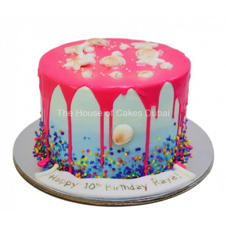Blue cake with neon pink dripping and seashells